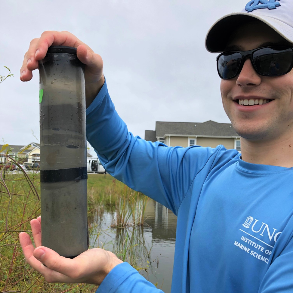Me holding a sediment core just extracted from a pond. The coring process created some air bubbles in this core that we had to carefully release